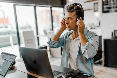 Man with headphones in front of a laptop